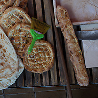 Round plain pide, long cheese-stuff pide and lavash cooling at a firin in eastern Turkey. The brush is for removing excess flour or kepek (bran) from the back of the bread before it's sold