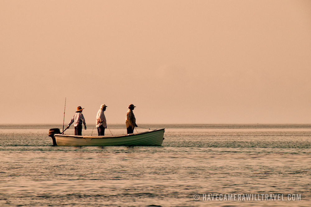 Three fishermen standing a small boat as they motor to a fishing spot on the edge of the reef at Swains Reef on the southern end of Australia's Great Barrier Reef. The later afternoon sun creates a warm, golden glow.