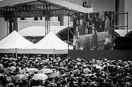"""Crowds follow the proceedings of the funeral of President Hugo Chávez on a giant screen outside the Military Academy in Caracas on the 8th March 2013.  President of Iran, Mahmud Ahmadinejad and President of Belarus are seen next to the coffin of the Venezuelan President. Chávez ruled Venezuela for 14 years, passed away on the 5th March 2013.  He revolutionized not only his nation but also other countries in Latin America, with his political views and what he called the """"21st Century Socialism"""", supported by the petrodollars from Venezuela's massive oil-reserves."""