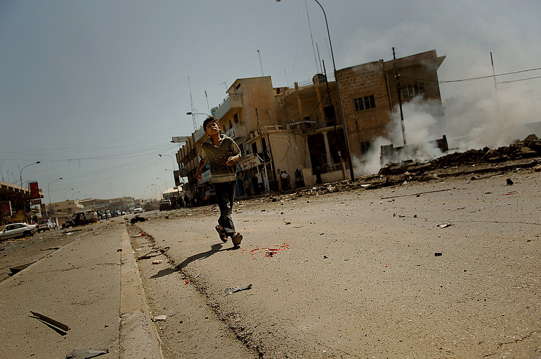A young Iraqi boy runs to his fathers truck after a car bomb detonated in Nabi Sheet, Mosul, Iraq on May 31, 2006. The car bomb wounded seven Iraqi Police, four critical, and 27 civilians, seven critical, according to Provincial Iraqi Police Headquarters Mosul Iraq. — © TSgt Jeremy Lock/