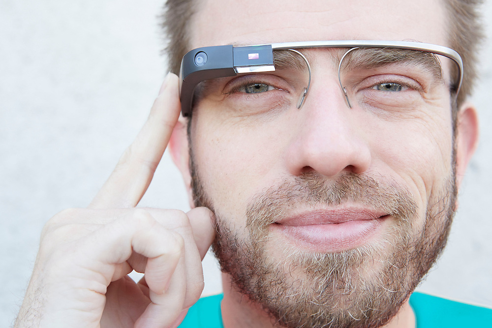 Close up portrait photograph of smiling man with beard with Google Glass eyewear