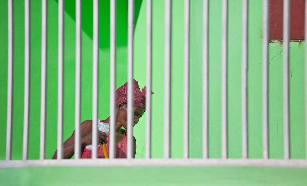 A woman sweeps the floor behind bars in a house in Anse a Galet, Ile La Gonave, Haiti