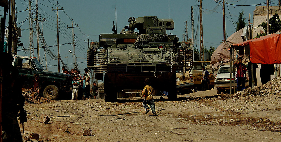 A young Iraqi boy runs across the road in front of a Stryker (an eight wheeled medium armored weapons combat troop transport vehicle) from Bravo Company 1/17th Infantry 172nd Stryker BDE Ft. Wainwright, Alaska, May 25, 2006 while patrolling the streets of Al Tanak, Mosul, Iraq. — © TSgt Jeremy Lock/