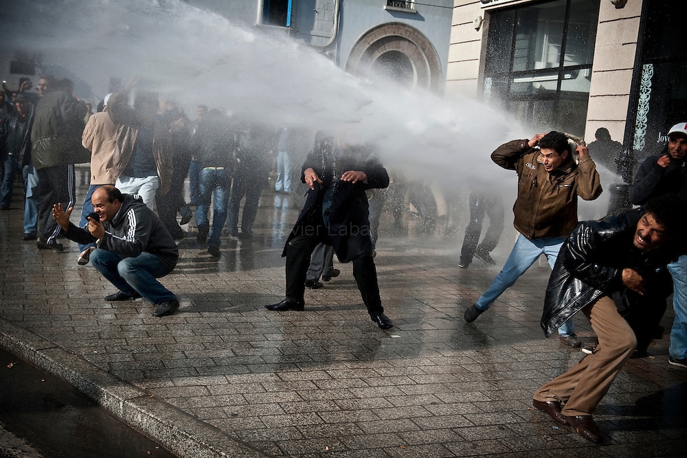 """Des opposants au régime de Ben Ali fuient pour éviter les canons à eaux des militaires, le 17 janvier 2011 sur l'avenue Bourguiba à Tunis, lors d'une manifestation de protestation contre la formation du nouveau gouvernement provisoire, réclamant """"le déracinement du système Ben Ali""""."""