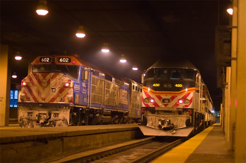 Two trains are side by side in preparation to depart from the north concourse of Chicago Union Station, underground next to the river.