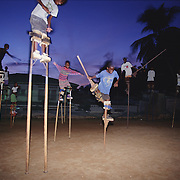 "Trinidad and Tobago ""MOKO JUMBIES: The Dancing Spirits of Trinidad"".(During nighttime practice, Ekwon Jeffrey rehearses the one foot jump.).A photo essay about a stilt walking school in Cocorite, Trinidad..Dragon Glen de Souza founded the Keylemanjahro School of Art & Culture in 1986. The main purpose of the school is to keep children off the streets and away from drugs..He first taught dances like the Calypso, African dance and the jig with his former partner Cathy Ann Samuel.  Searching for other activities to engage the children in, he rediscovered the art of stilt-walking, a tradition known in West Africa as the Moko Jumbies , protectors of the villages and participants in religious ceremonies. The art was brought to Trinidad by the slave trade and soon forgotten..Today Dragon's school has over 100 members from age 4 and up..His 2 year old son Mutawakkil is probably the youngest Moko Jumbie ever. The stilts are made by Dragon and his students and can be as high as 12-15 feet. The children show their artistic talents mostly at the annual Carnival, which today is unthinkable without the presence of the Moko Jumbies. A band can have up to 80 children on stilts and they have won many of the prestigious prizes and trophies that are awarded by the National Carnival Commission. Designers like  Peter Minshall , Brian Mac Farlane and Laura Anderson Barbata create dazzling costumes for the school which are admired by thousands of  spectators. Besides stilt-walking the children learn the limbo dance, drumming, fire blowing and how to ride  unicycles..The school is situated in Cocorite, a suburb of Port of Spain, the capital of Trinidad and Tobago..all images © Stefan Falke"