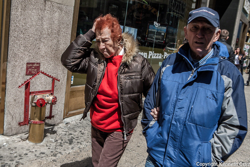 An older couple walking down 7th Avenue in New York City.  She's looking particularly stressed.