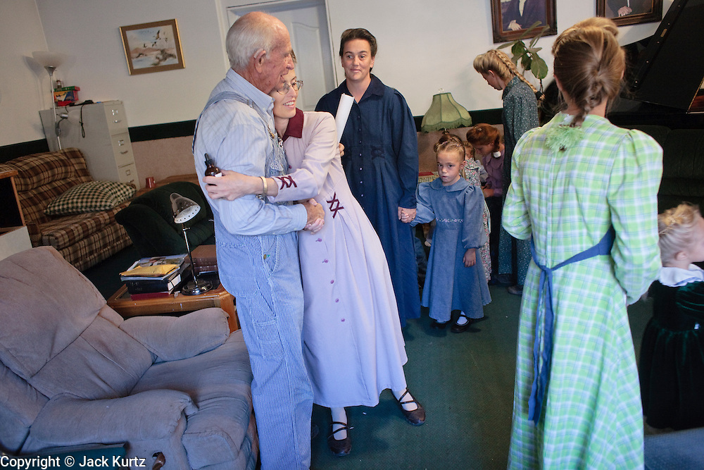 """Sept 8, 2008 -- COLORADO CITY, AZ:  JOSEPH JESSOP, patriarch of the Jessop family, polygamist members of the FLDS, gets hugs from his children and wives after morning prayers in their home. Colorado City and the neighboring town of Hildale, UT, are home to the Fundamentalist Church of Jesus Christ of Latter Day Saints (FLDS) which split from the mainstream Church of Jesus Christ of Latter Day Saints (Mormons) after the Mormons banned what they call """"Celestial Marriage"""" (polygamy) in 1890 so that Utah could gain statehood into the United States. The FLDS Prophet (leader), Warren Jeffs, has been convicted in Utah of """"rape as an accomplice"""" for arranging the marriage of teenage girl to her cousin and is currently on trial for similar, those less serious, charges in Arizona. After Texas child protection authorities raided the Yearning for Zion Ranch, (the FLDS compound in Eldorado, TX) many members of the FLDS community in Colorado City/Hildale fear either Arizona or Utah authorities could raid their homes in the same way. Older members of the community still remember the Short Creek Raid of 1953 when Arizona authorities using National Guard troops, raided the community, arresting the men and placing women and children in """"protective"""" custody. After two years in foster care, the women and children returned to their homes. After the raid, the FLDS Church eliminated any connection to the """"Short Creek raid"""" by renaming their town Colorado City in Arizona and Hildale in Utah. The Jessops are a polygamous family and members of the FLDS.   Photo by Jack Kurtz / ZUMA Press"""