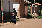 Campesina woman walking in the street in Postrervalle, Santa Cruz, Bolivia