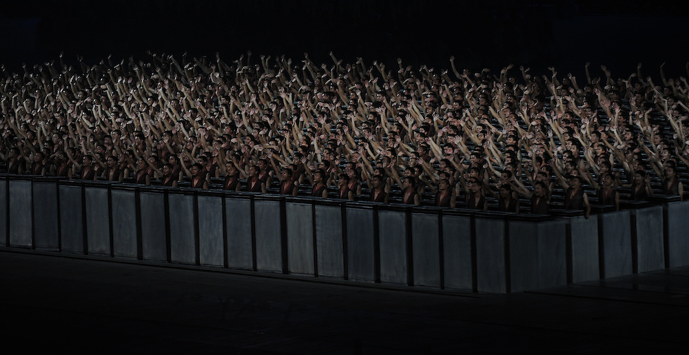 2008 OLYMPIC GAMES - OPENING CEREMONIES - 080808 - Performers who took part in a dramatic display meant to show China's influence in moveable type printing acknowledge the crowd after they used boxes to simulate the type.