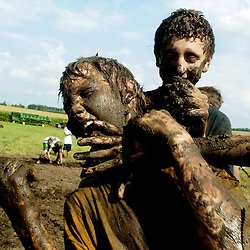 Tyler Solsma of Sanborn, Iowa laughs as Adam Bousema, also of Sanborn, and another friend smear his face with mud. Solsma and about 30 others got down and dirty in the Youth Council Mud Volleyball Tournament at the O'Brien County Fair in Primghar.
