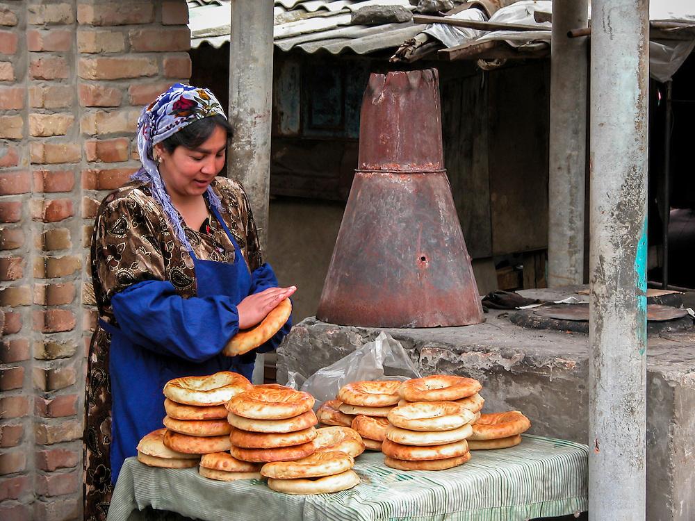 Portrait of a Tajik woman selling flat bread (non) loaves in a market in western Tajikistan