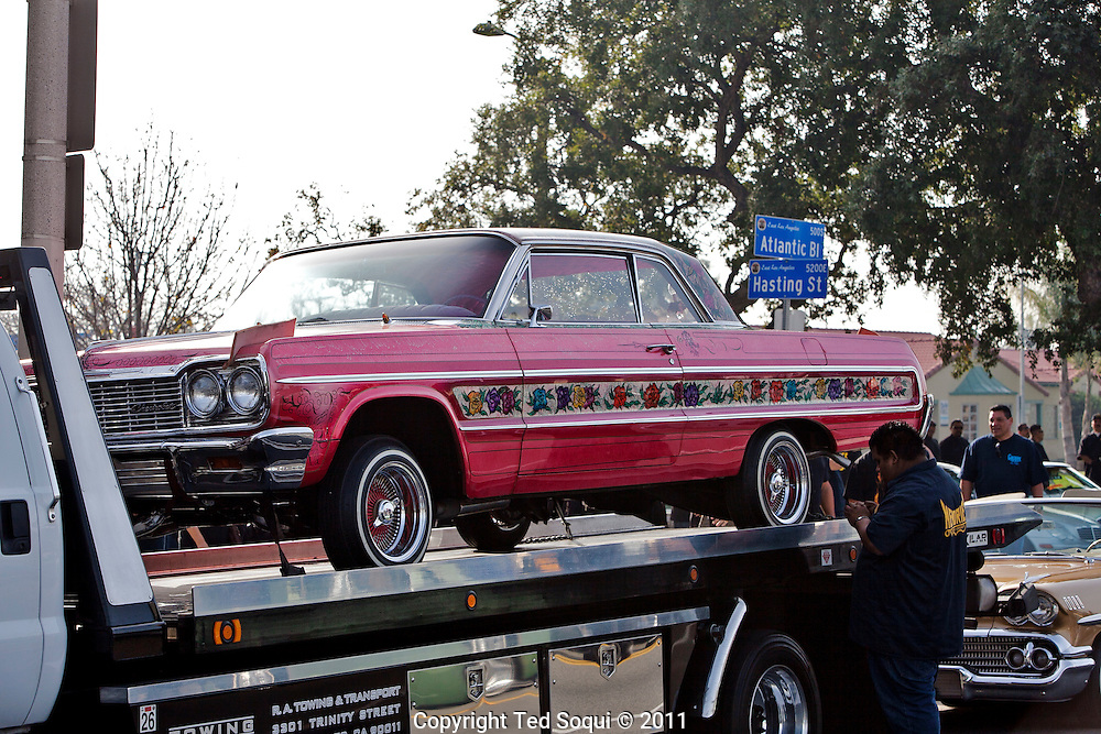 "The ""Gypsy Rose""  on a flatbed truck..Funeral procession for lowrider pioneer and founding member of the Imperials Car Club, Jesse Valadez..Valadez's  lowrider, ""Gypsy Rose"" a 1964 Chevy Impala with painted roses on each side and a bright pink interior, is considered to be the world's most famous lowrider by many car enthusiast. It was featured on the sitcom ""Chico and the Man,"" and took two and a half years to complete. .Hundreds of lowriders from the Imperial and fellow car clubs led a procession through East L.A., with the ""Gypsy Rose"" leading on a flat bed truck."