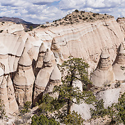 "Hoodoos panorama. See fantastic hoodoos and a great slot canyon in Kasha-Katuwe Tent Rocks National Monument, in New Mexico, USA. Hike the easy Cave Loop Trail plus Slot Canyon Trail side trip (3 miles round trip), 40 miles southwest of Santa Fe, on the Pajarito Plateau. Distinctive cone-shaped caprocks protect soft pumice and tuff beneath. Geologically, the Tent Rocks are made of Peralta Tuff, formed from volcanic ash, pumice, and pyroclastic debris deposited over 1000 feet thick from the Jemez Volcanic Field, 7 million years ago. Kasha-Katuwe means ""white cliffs"" in the Pueblo language Keresan. This panorama was stitched from 6 overlapping photos."