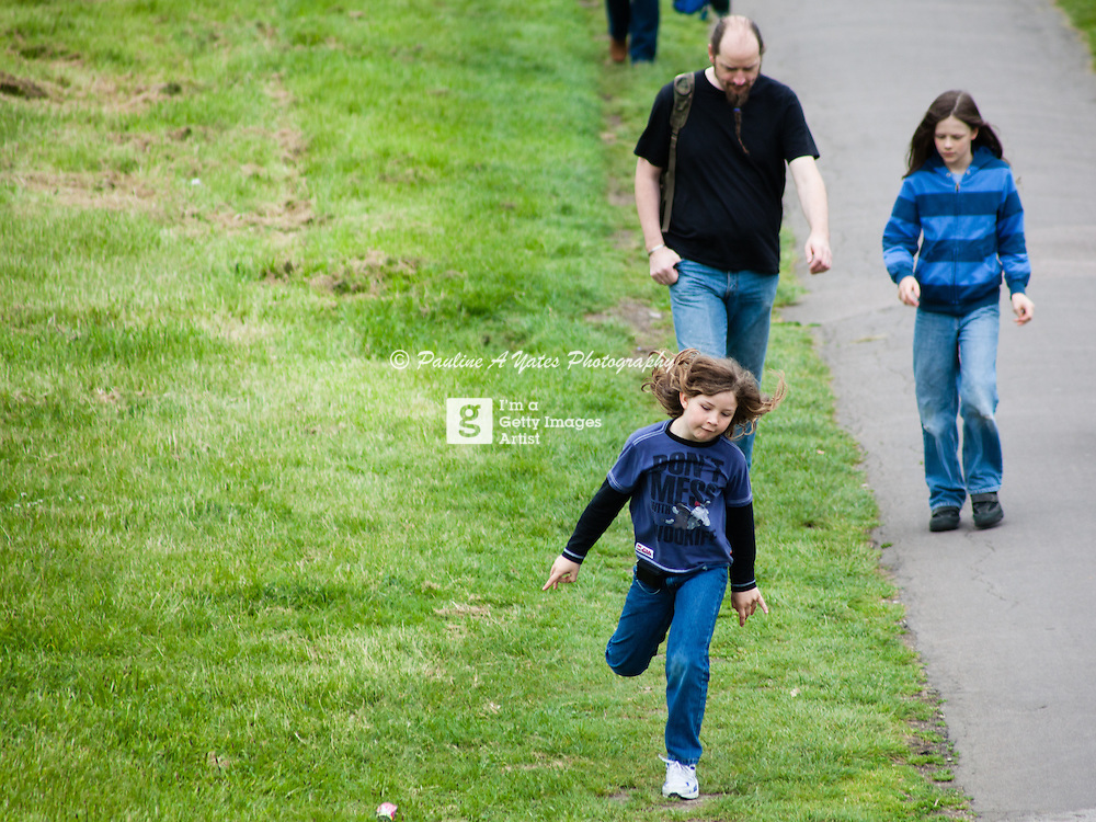 A young child jumps along while her father walks with her older sister