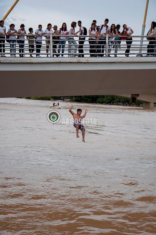 """Crianca pula da Passarela Joaquim Macedo sobre o Rio Acre. A enchente do Rio Acre em 2012 e a maior da historia em numero de atingidos. """"Enchente"""" """"ou cheia"""" e, geralmente, uma situacao natural de transbordamento de agua do seu leito natural, provocada geralmente por chuvas intensas e continuas./Acre River flooding.A flash flood is a rapid flooding of geomorphic low-lying areas?washes, rivers, dry lakes and basins. It may be caused by heavy rain associated with a storm, hurricane, or tropical storm."""