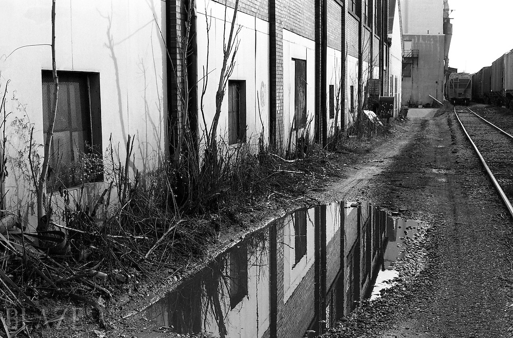 Train tracks and reflection in deserted alleyway.