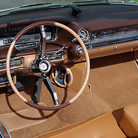 The steering wheel, dashboard and driver's-side seating area of a restored 1960 Cadillac convertible. WATERMARKS WILL NOT APPEAR ON PRINTS OR LICENSED IMAGES.