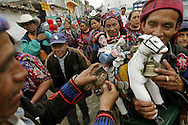 Men dressed in traditional Mayan costume make their way down one of the streets in Chichicastenango in a procession with traditional values.