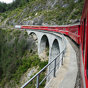 "Playfully, Switzerland advertises the Glacier Express as ""the slowest express train in the world."" Opened in 1930, this narrow gauge railway connects the mountain resorts of Zermatt and St. Moritz in the Swiss Alps, from the Matterhorn to Piz Bernina, frequently applying a rack-and-pinion system to go up and down steep grades. An especially curlycue portion of the Glacier Express route is honored as a UNESCO World Heritage Site: the ""Rhaetian Railway in the Albula / Bernina Landscapes"". Jointly operated by the Matterhorn Gotthard Bahn (MGB) and Rhaetian Railway (RhB), the 7.5 hour railway journey crosses 291 bridges, enters 91 tunnels and reaches 2033 m (6670 ft) elevation at Oberalp Pass."