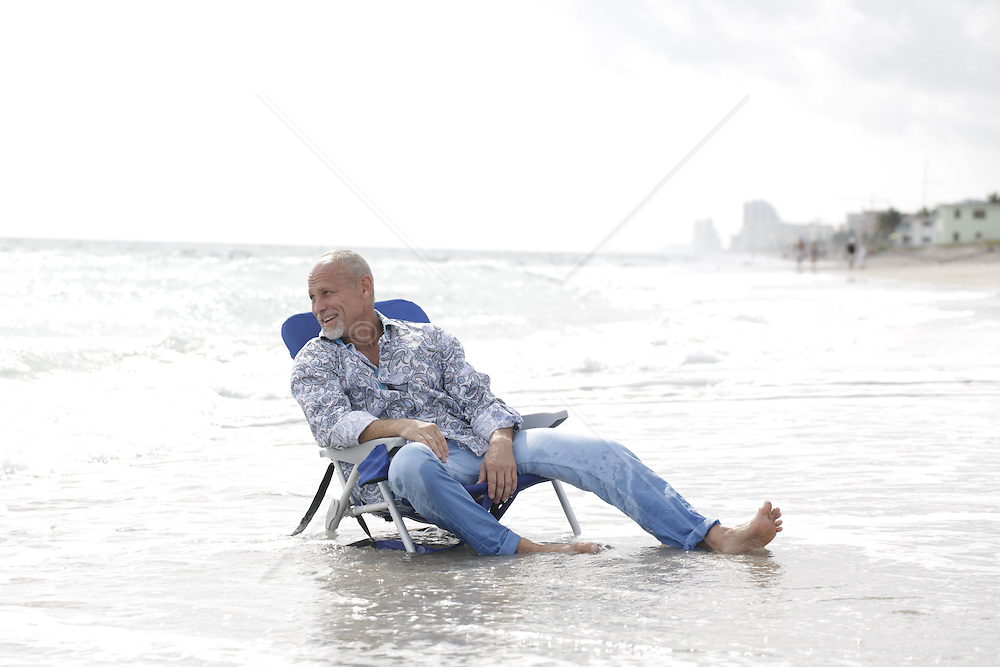handsome older man relaxing in a chair in the ocean