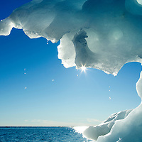 Canada, Manitoba, Churchill, Sun illuminates melting sea ice on Hudson Bay on summer evening