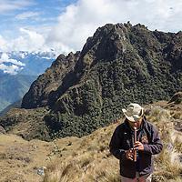 Peru, Hiking party's guide playing flute at summit of Abra de Runkuracay pass along Inca Trail to Machu Picchu