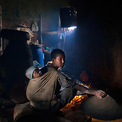 Fifteen-year-old Destaye prepares a meal while her son rests on her back inside their home near Bahir Dar, Ethiopia on Aug. 10, 2012. Destaye and her husband Addisu, 27, divide their time between working in the fields and taking care of their 6-month-old baby. Like many other young couples, they tend to the domestic, economic and personal demands of being young parents. At the time of their marriage, when Destaye was age 11, she was still in school and her husband expressed interest in letting her continue her education. Since the birth of their son, however, she has had to confine her life exclusively to being a wife and mother.
