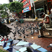 A man sits on a bench in the pedestrian shopping zone of Panama City on Wednesday, September 5, 2007. (Photo/Scott Dalton).