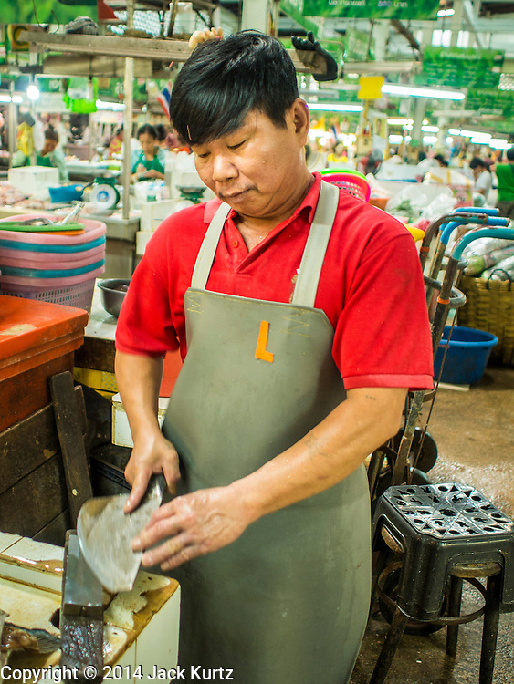 09 DECEMBER 2014 - THONBURI, BANGKOK, THAILAND: A fish seller sharpens a cleaver in his stall in a market in the Thonburi section of Bangkok, near the Wong Wian Yai Train Station.    PHOTO BY JACK KURTZ
