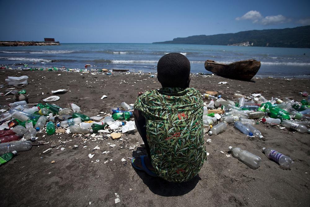 A kid crouches on a litter-strewn beach in Jacmel, Haiti