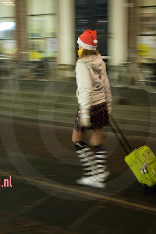 meisje dame loopt met kerstmuts en koffer over straat
