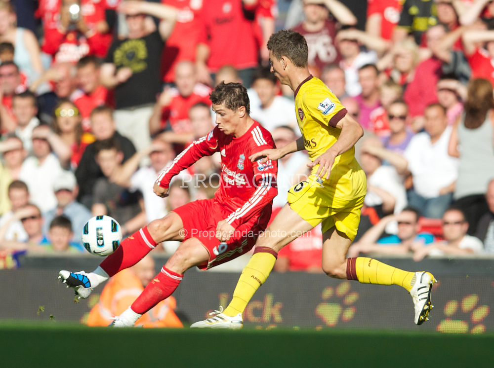 LIVERPOOL, ENGLAND - Sunday, August 15, 2010: Liverpool's Fernando Torres clips the ball past Arsenal's Laurent Koscieiny, who handled the ball resulting in a sending off, during the Premiership match at Anfield. (Pic by: David Rawcliffe/Propaganda)