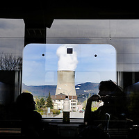 Passengers on a passing train and G&ouml;sgen Nuclear Power Plant (Kernkraftwerk G&ouml;sgen), with smoke rising from its cooling tower. <br /> The Swiss are due to vote shortly in a referendum whether to quit nuclear power, which via its five reactors, on four sites, provide almost 40% of the country's power
