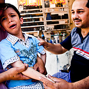 Christian tattooer just finished tattooing a young boy with a small cross on his arm outside the church. It is a Coptic tradition to be tattooed with a small orthodox cross on your arm when you are young