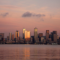 WA10049-00...WASHINGTON - Light reflecting off the highrises in downtown Seattle onto Elliott Bay at sunset.