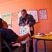 Khalid is having one on one instruction in the Mercy Corps resource room. His volunteer instructor, Ibrahim (also a refugee), has over 35 years of teaching experience in Syria. Zaatari camp for Syrian refugees, Jordan, March 2014.