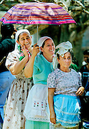 LA LAGUNA, CHALATENANGO, EL SALVADOR- MAY 2000: Three El Salvadoran women use an umbrella to try to keep the hot midday sun of their heads while waiting for a state run medical clinic to offer free health screenings in La Laguna. It is one way the government said it can help ease the long tensions of the civil war in FMLN, Farabundo Martí National Liberation Front, controlled Chalatenango state.  (Photo by Robert Falcetti). .