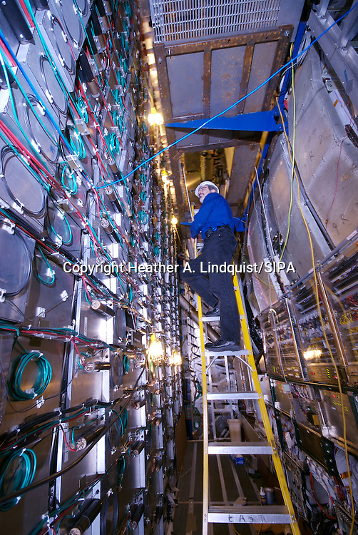 "18th August 2009 - Batavia, IL..DZero collision hall and DZero control room, at Fermilab...George Ginther from Fermilab standing on a ladder next to the Forward Muon Detectors make up what is referred to as the ""Cathedral"" at DZero.  ..More than two million times a second, proton-antiproton collisions create showers of new particles at the center of both CDF and DZero detectors, which record each particle's flight path, energy and electric charge. Working in shifts, physicists monitor the proper functioning of the detectors 24 hours a day. In 1995, physicists from both experiments observed the first top quarks ever produced by accelerators. ..Photo Credit: Heather A. Lindquist/SIPA.."
