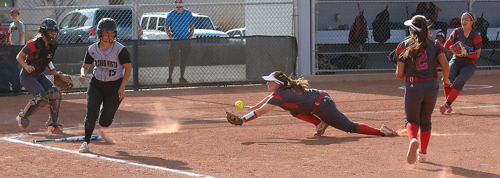 gbs032117f/SPORTS -- Sandia pitcher Victoria Reyes dives for the bunt of Volcano Vista's Samantha Trujillo, 15, in the 2nd inning as catcher Bailey Martinez, first baseman Kara Rodeheaver, 2, and third baseman Jordan Ramkowsky defend during the play. Trujillo made it to first safe during the game at Volcano Vista on Tuesday, March 21, 2017. (Greg Sorber/Albuquerque Journal)
