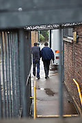 A prisoner in handcuffs is taken away from court after his hearing to a waitng prison van.