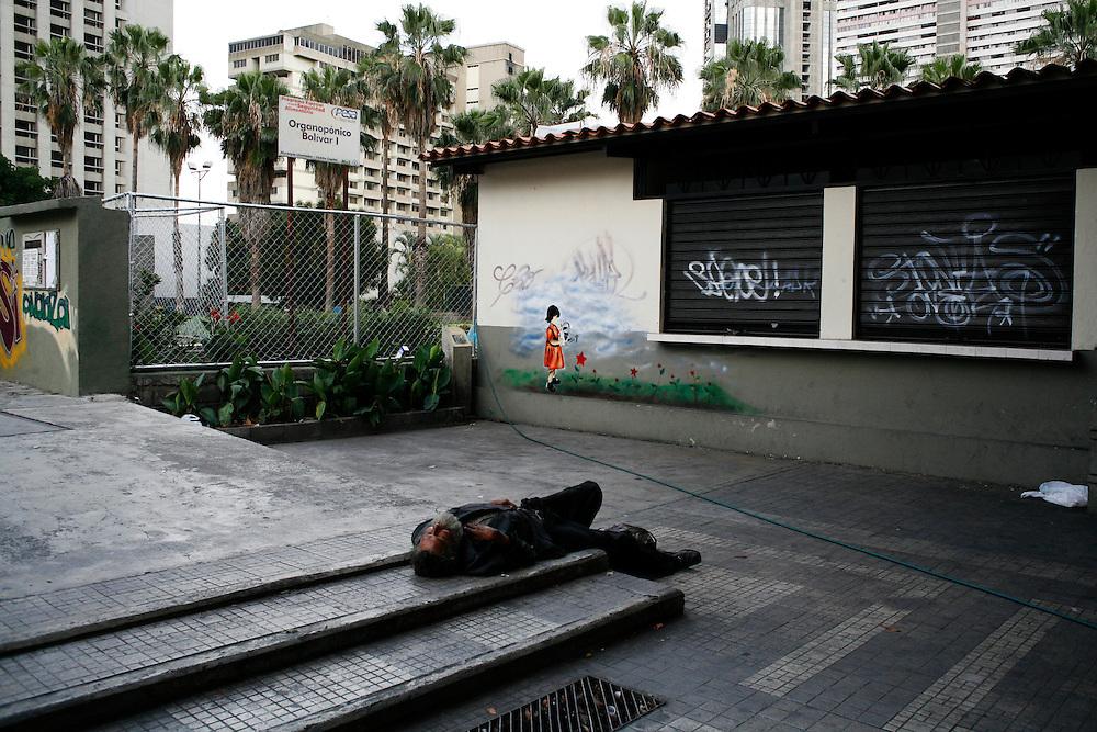 A homeless man sleeps near a state-run garden in downtown Caracas.
