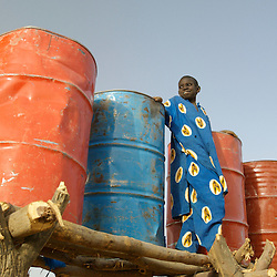 Ibrahim stands next to water tanks next to a garden Oxfam supported in the village of  Intadeynen, March 14, 2007 in Mali.