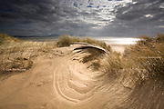 Nominated in 10th (2017) International Colour Awards (Nature category) <br /> <br /> Wind formed shapes in the Llanddwyn sand dunes, with crepuscular rays in the skies behind.