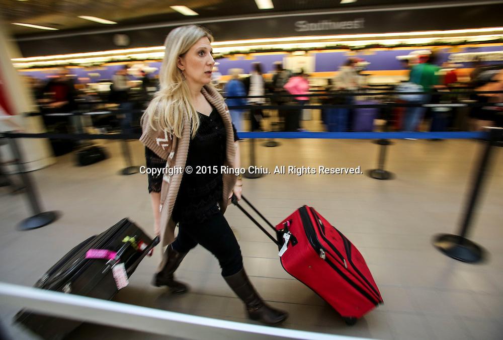 12月22日,在美国洛杉矶国际机场,一名旅客赶紧向航空公司办理手续。根据南加州汽车俱乐部(Automobile Club of Southern California) 发表最新报告,在圣诞新年假期期间(12月23日至1月3日),全加州将创纪录有1230万民众出游50英里以上的目的地,其中南加州将佔760万民众。洛杉矶国际机场官员同时表示,他们亦预计有创纪录350万人次在假日期间使用机场往返国内国外,比去年同期增加7.9%,将使洛杉矶国际机场成为全美最繁忙的机场。新华社发 (赵汉荣摄)<br /> A holiday traveler rushes to check in at Los Angeles International Airport on Tuesday, December 22, 2015 in Los Angeles, the United States. A record 12.3 million California residents -- 7.6 million of them from Southern California -- will travel 50 miles or more between Dec. 23 and Jan. 3, the Automobile Club of Southern California said. Los Angeles International Airport officials, meanwhile, said they expect a record 3.5 million passengers to pass through the airport during the holiday travel season, up 7.9 percent from last year. That would make LAX the nation's busiest over the holidays, officials said. (Xinhua/Zhao Hanrong)(Photo by Ringo Chiu/PHOTOFORMULA.com)<br /> <br /> Usage Notes: This content is intended for editorial use only. For other uses, additional clearances may be required.