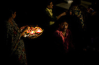 Flower sellers mingle with pilgrims just prior to the start of the nightly arti, or puja, ceremony at the main ghat known as Dasashwamedh Ghat along the Ganges River in Varnasi, India.