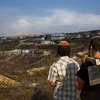 Two Israeli settlers look at the Havat Gilad settlement.