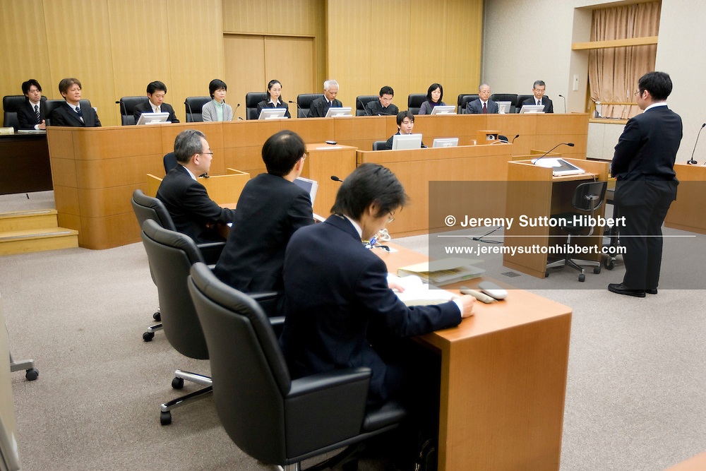 """The three judges and six 'lay judges' ( members of the public forming the jury), in background of photo,  preside over courtroom proceedings during a mock trial where the defendant was accused of """"accidental mortality"""" (and found innocent), in Saitama District Court, in Urawa town, Saitama city, Japan, Friday 27th February 2009. The mock trial is part of the process of introducing the 'lay judges jury system' to the Japanese law system. Trials with 'lay judge juries' will begin in May 2009."""