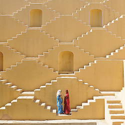 Jasmin (wearing red) and Manisha Singh (white and blue sari)stand in an ancient water well in the city of Japiur in India's Rajasthan Thar desert. (Photo by Ami Vitale)