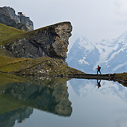 "A hiker and peaks of Eiger and Mönch reflect in Grauseeli lake below Birg, the midway station on the Schilthorn cable car in the Berner Oberland, Switzerland, the Alps, Europe. The Bernese Highlands are the upper part of Bern Canton. UNESCO lists ""Swiss Alps Jungfrau-Aletsch"" as a World Heritage Area (2001, 2007)."